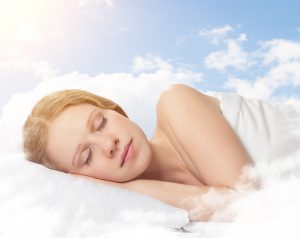portrait of a beautiful young woman sleeping on a cloud in the sky